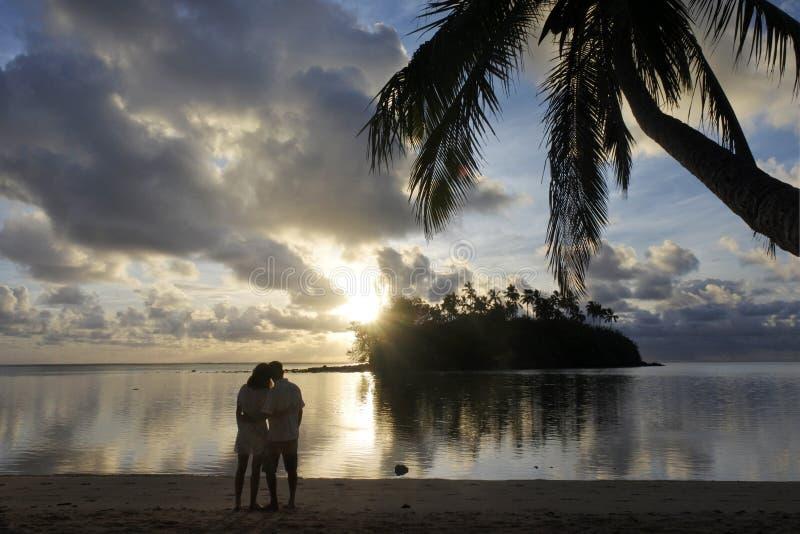 Las miradas de los pares de la luna de miel en la salida del sol de un Pacífico tropical son imagenes de archivo
