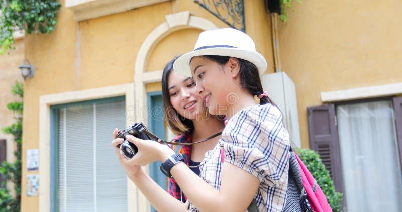 Las mochilas asi?ticas de las mujeres que caminan juntas y felices est?n tomando la foto y mirando la imagen, relaje el tiempo en fotografía de archivo libre de regalías