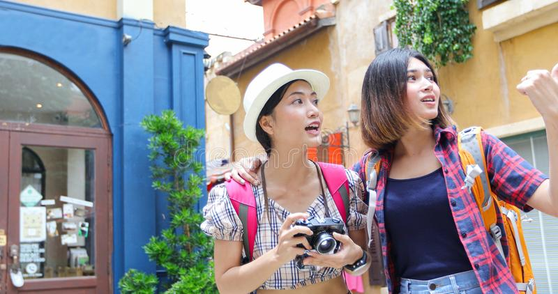 Las mochilas asi?ticas de las mujeres que caminan juntas y felices est?n tomando la foto y mirando la imagen, relaje el tiempo en foto de archivo libre de regalías
