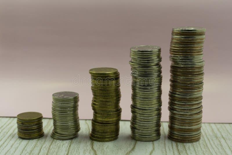 Las monedas apilan delante del dinero de los ahorros del libro de la cuenta bancaria del concepto de las monedas para la escalera imagen de archivo