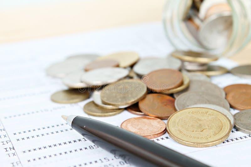 Las monedas dispersaron del tarro y de la pluma de cristal en libreta de banco de cuenta de ahorro o el estado financiero imagenes de archivo