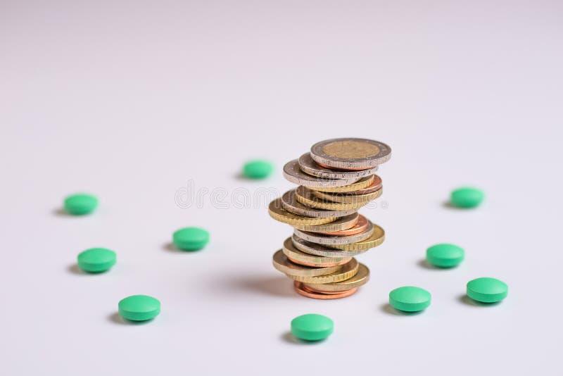 Las monedas se colocan entre ellos mismos en diversas posiciones al lado de las píldoras verdes imágenes de archivo libres de regalías
