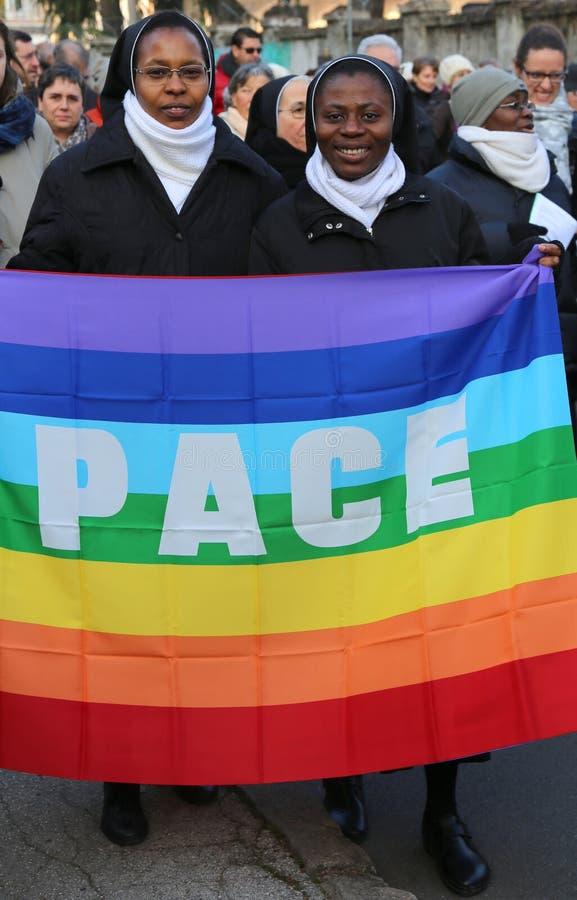 Las monjas africanas de marzo de paz dos con la bandera con la palabra ESTABLECEN EL PASO de paz fotografía de archivo libre de regalías