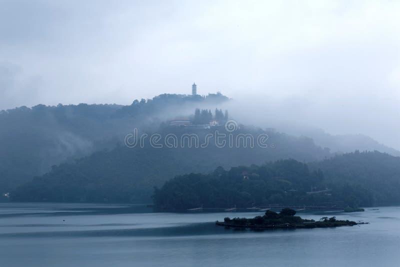 Las montañas brumosas por Sun están en la luna el lago en una mañana de niebla, con una pagoda en la cima de la montaña distante foto de archivo libre de regalías