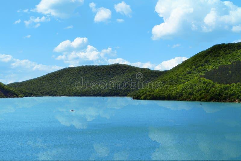 Las montañas con el bosque verde en un lago apuntalan en el cielo con las nubes fondo, nubes reflejan en agua imagenes de archivo