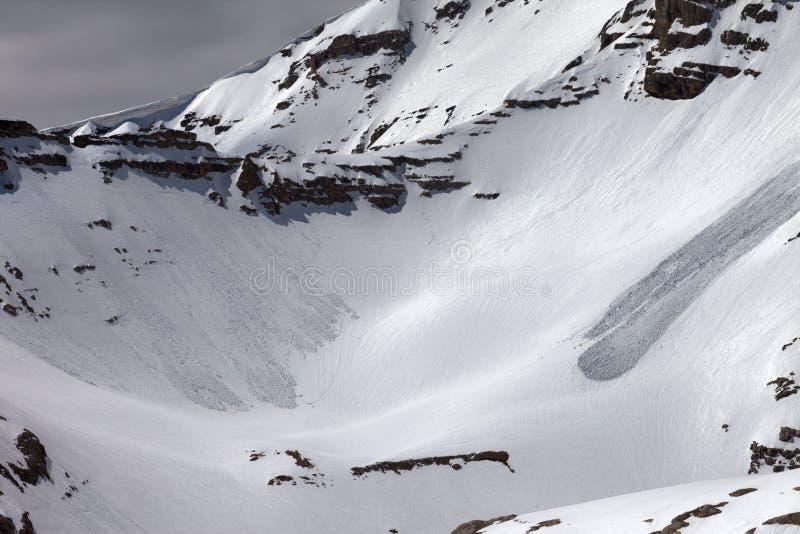 Las montañas con nieve adornan con cornisa y los rastros de avalanchas foto de archivo
