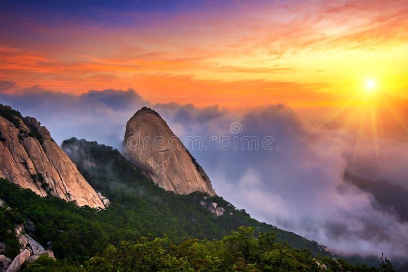 Las montañas de Bukhansan son cubiertas por la niebla y la salida del sol de la mañana foto de archivo libre de regalías