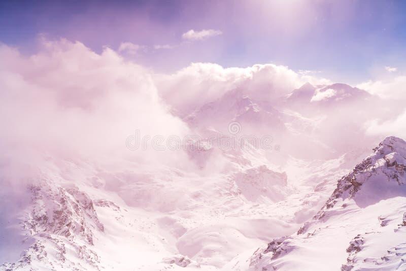Las montañas del cielo del invierno enrollan extremadamente altamente el fondo del extracto del bokeh del haz del sol de las nube fotos de archivo libres de regalías