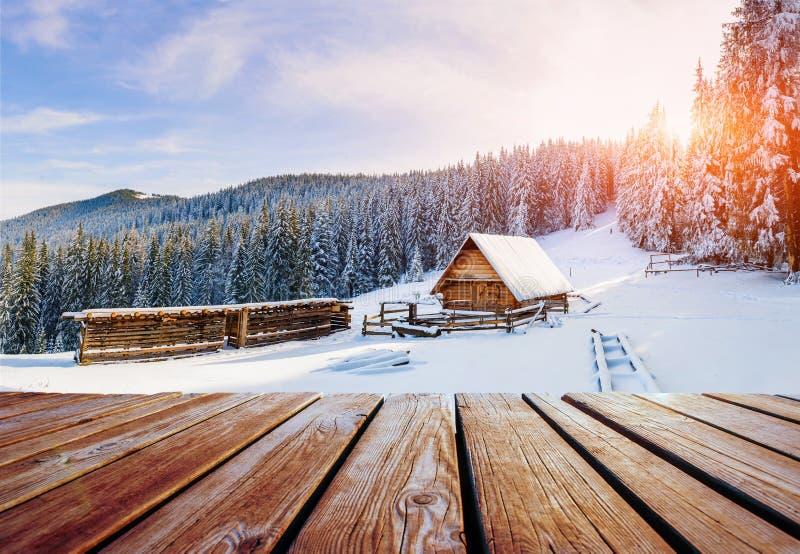 Las montañas del invierno ajardinan con un bosque nevoso y una choza de madera imagenes de archivo