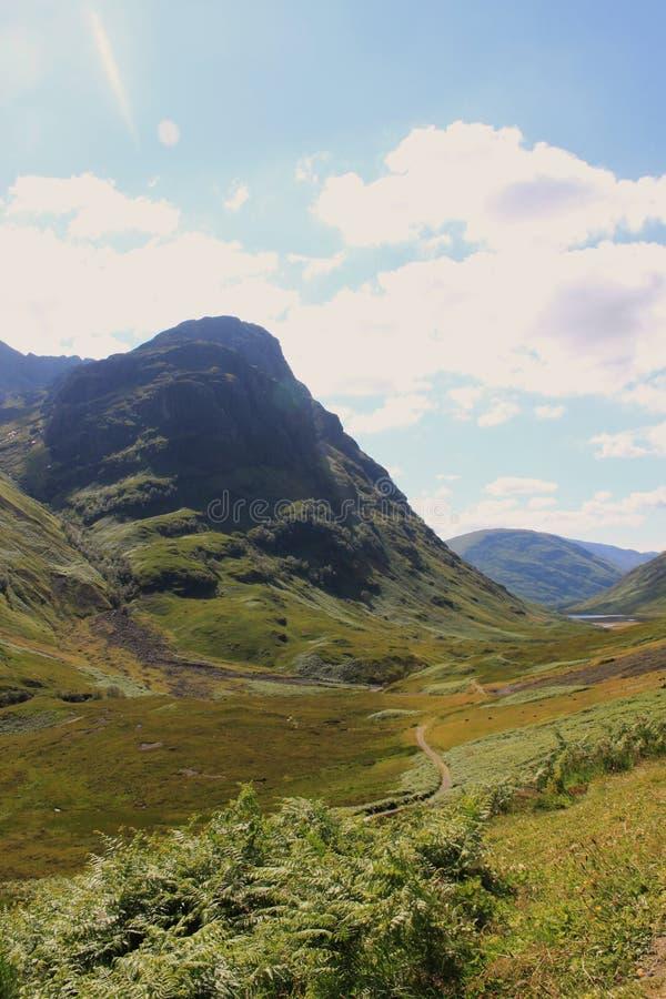 Las montañas escocesas ajardinan en el verano - camino en el valle fotos de archivo libres de regalías