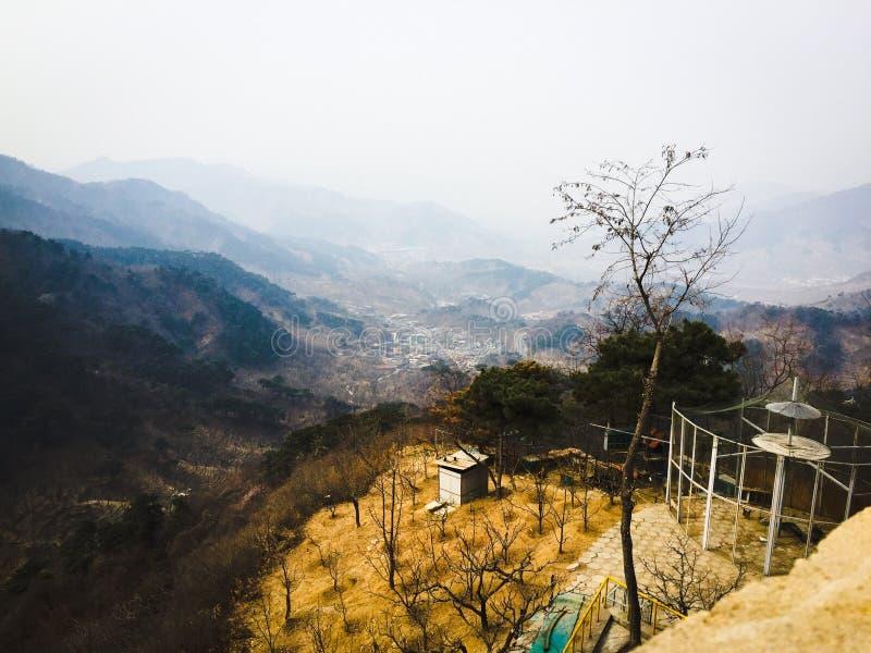 las montañas, los árboles, y el pueblo fotografía de archivo libre de regalías