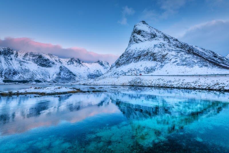 Las montañas nevadas hermosas y el cielo azul reflejaron en agua imagen de archivo