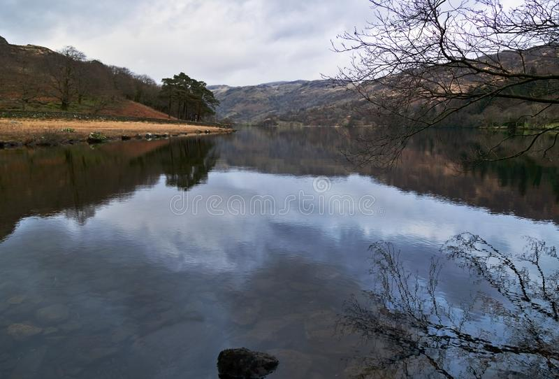 Las montañas reflejaron en aguas de una calma del lago Llyn Gwynant fotos de archivo