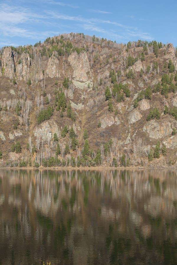Las monta?as reflejaron en el agua y el cielo azul fotografía de archivo libre de regalías