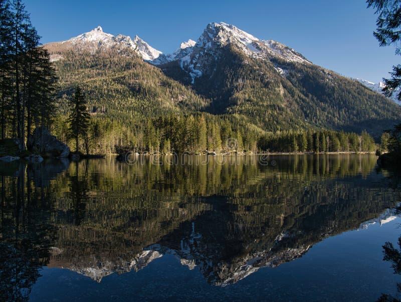 Las montañas se reflejan en el lago claro fotos de archivo