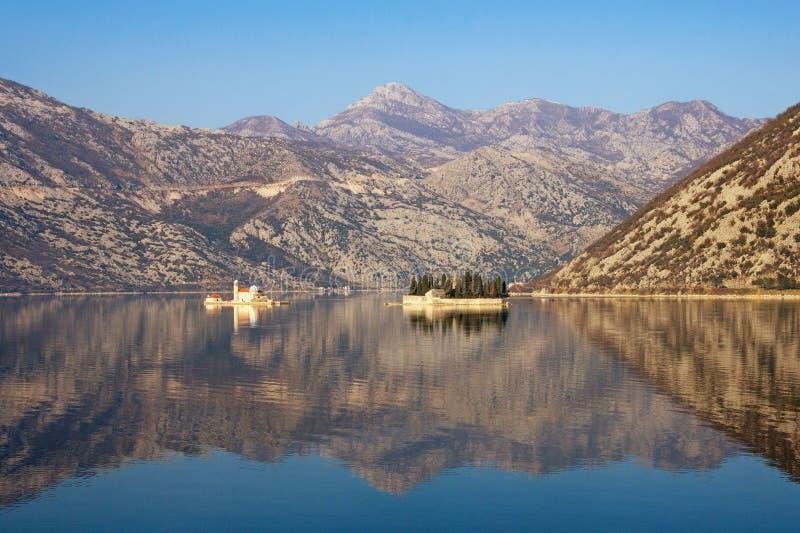 Las montañas y dos islas de nuestra señora de las rocas y San Jorge se reflejan en la bahía de Kotor en día de invierno soleado m foto de archivo libre de regalías