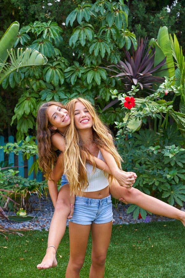 Las muchachas adolescentes de los mejores amigos llevan a cuestas en patio trasero fotografía de archivo libre de regalías