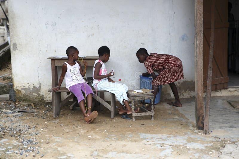 Las muchachas africanas se sientan delante de una casa foto de archivo