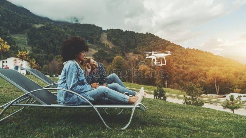 Las muchachas al aire libre están registrando el vídeo para sus vlogs usando abejón imagen de archivo libre de regalías