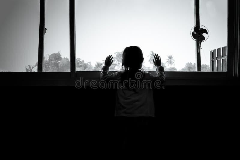 Las muchachas asiáticas del niño se están colocando en la oscuridad imagen de archivo libre de regalías