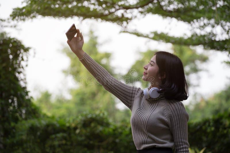 Las muchachas asiáticas felices están tomando las fotos con el teléfono elegante imagen de archivo