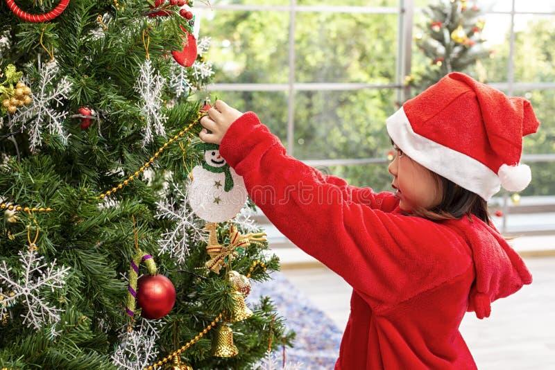 Las muchachas asiáticas que llevan los vestidos rojos están adornando los árboles de navidad Ni?os que abren presentes el v?spera imagen de archivo