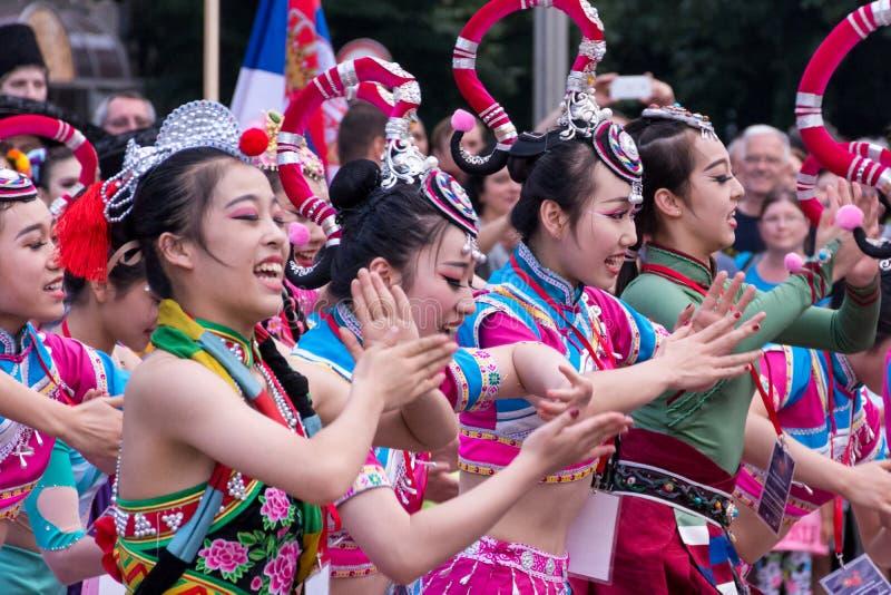 Las muchachas chinas hermosas bailan danza popular en trajes rosados tradicionales imagen de archivo