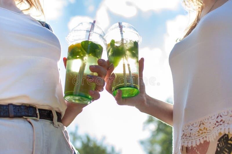 Las muchachas colocan y sostienen los vidrios plásticos con mojito, ellas tintinean los vidrios con las bebidas, primer de bebida imagenes de archivo