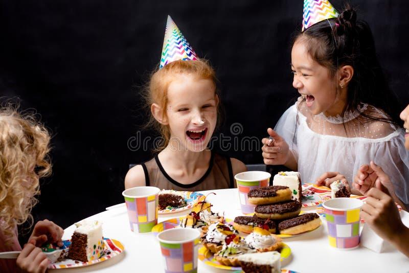 Las muchachas con la torta en narices están riendo mientras que se sientan en la tabla foto de archivo libre de regalías