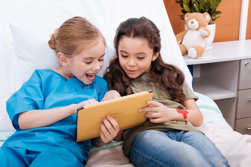 Las muchachas cuidan y paciente que usa la tableta digital mientras que mienten en cama de hospital fotografía de archivo