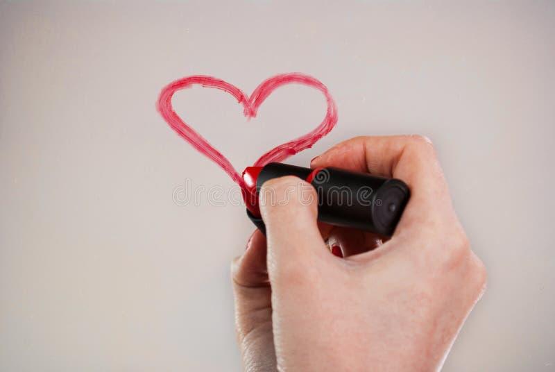 Las muchachas dan con el corazón rojo del dibujo del lápiz labial en el espejo para el día de tarjetas del día de San Valentín fotos de archivo libres de regalías