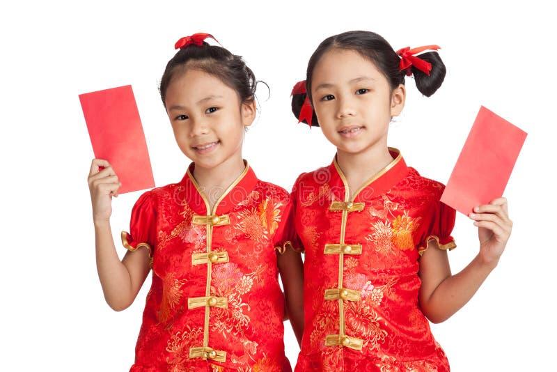 Las muchachas de los gemelos del asiático en cheongsam chino se visten con el sobre rojo fotos de archivo