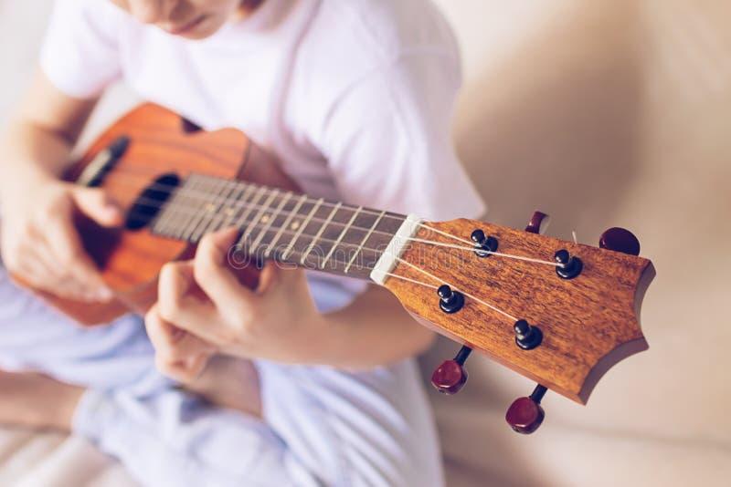 Las muchachas de las manos tocan la guitarra Un ni?o aprende tocar la guitarra Foco selectivo Primer El concepto de m?sica y de a fotografía de archivo libre de regalías