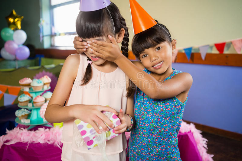Las muchachas del cumpleaños de la cubierta de la muchacha observan y ofreciendo un regalo foto de archivo