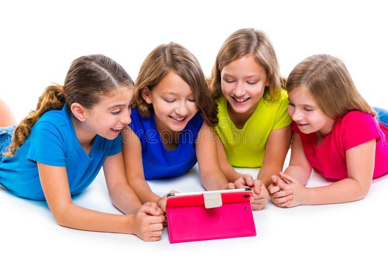 Las muchachas del niño de las hermanas con tecnología hacen tabletas jugar de la PC feliz imagenes de archivo
