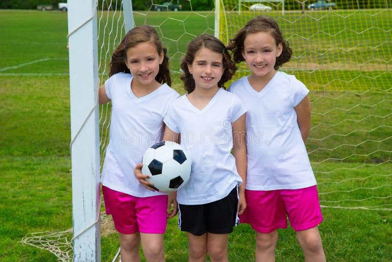 Las muchachas del niño del fútbol del fútbol combinan en el fileld de los deportes foto de archivo
