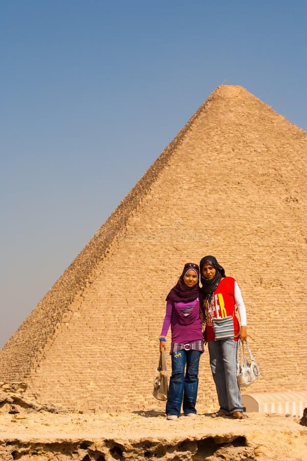 Las muchachas egipcias presentan la pirámide Cheops imagen de archivo libre de regalías