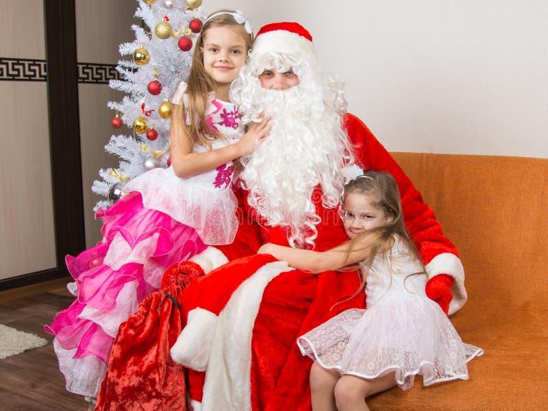 Las muchachas en vestidos hermosos abrazan a Santa Claus que se sienta en un sofá fotografía de archivo