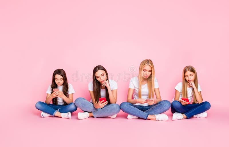 Las muchachas enfocadas cansadas aburridas tristes atractivas agradables que se sentaban en piso cruzaron las piernas que charlab foto de archivo