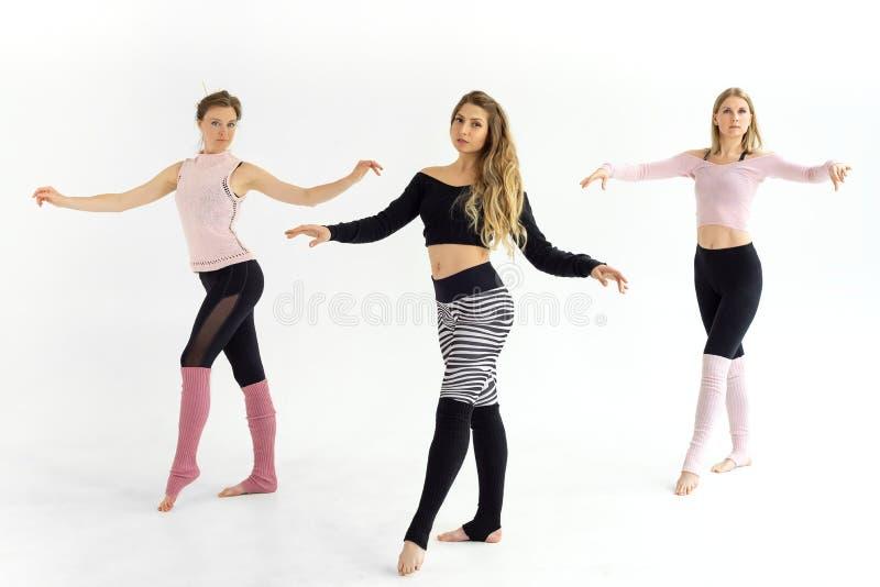 Las muchachas entrenan a pilates de la yoga, enganchan a danzas imágenes de archivo libres de regalías