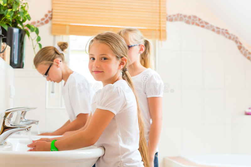 Las muchachas están lavando las manos en el baño imagen de archivo libre de regalías