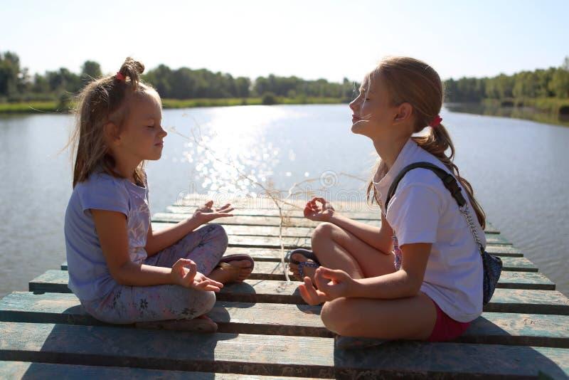 Las muchachas están reflexionando sobre el embarcadero en el lago fotos de archivo libres de regalías