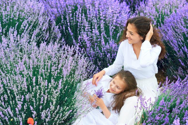 Las muchachas est?n en el campo de flor de la lavanda, paisaje hermoso del verano fotografía de archivo libre de regalías