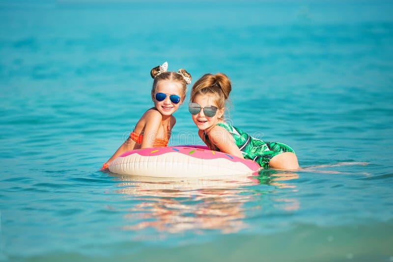 Las muchachas felices alegres tienen un resto en el mar fotos de archivo