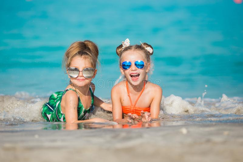 Las muchachas felices alegres tienen un resto en el mar fotografía de archivo libre de regalías