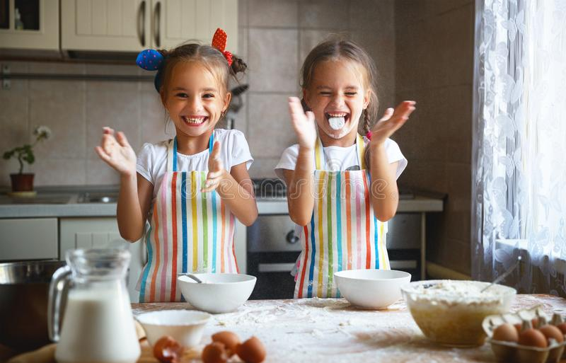 Las muchachas felices de los niños de las hermanas cuecen las galletas, amasan la pasta, ingenio del juego foto de archivo libre de regalías