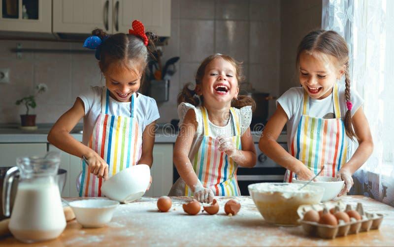 Las muchachas felices de los niños de las hermanas cuecen las galletas, amasan la pasta, ingenio del juego fotos de archivo libres de regalías