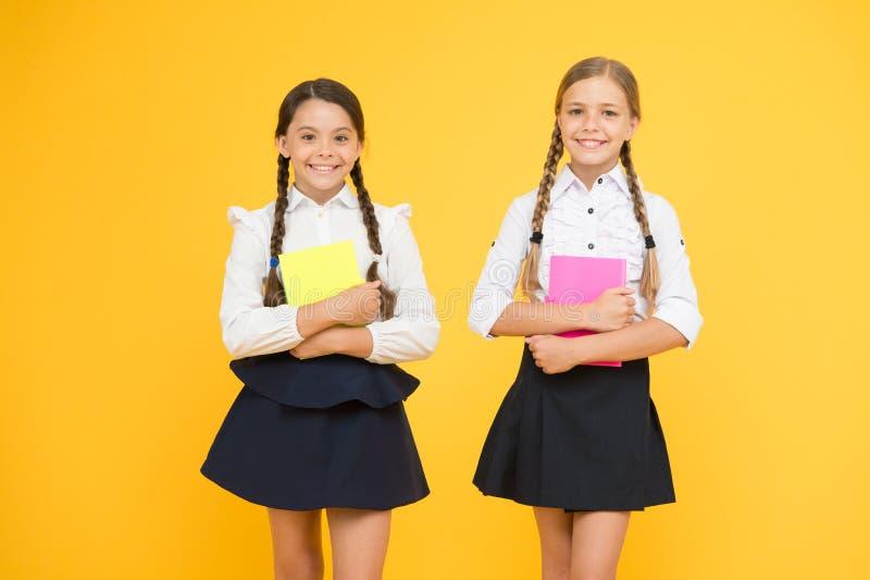 Las muchachas felices estudian con la libreta trabajo de proyecto junto lección de la literatura Lectura y escritura pequeños niñ foto de archivo