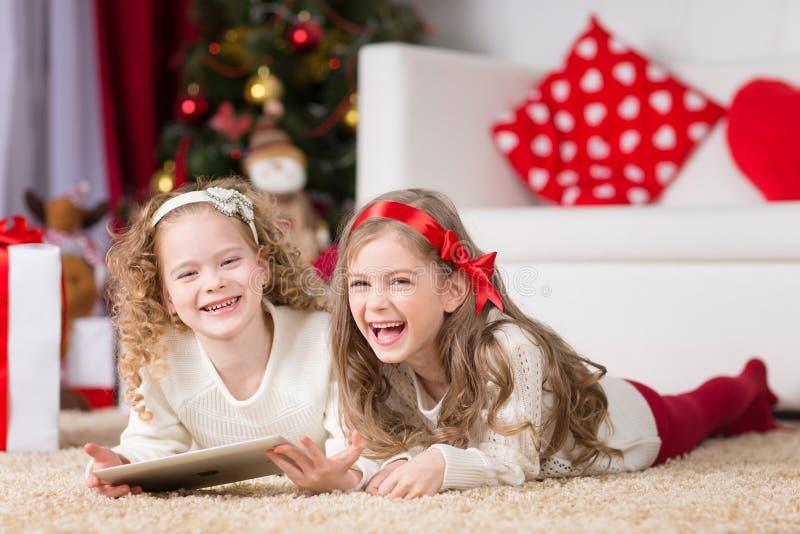 Las muchachas felices que jugaban en la Navidad adornaron el sitio foto de archivo