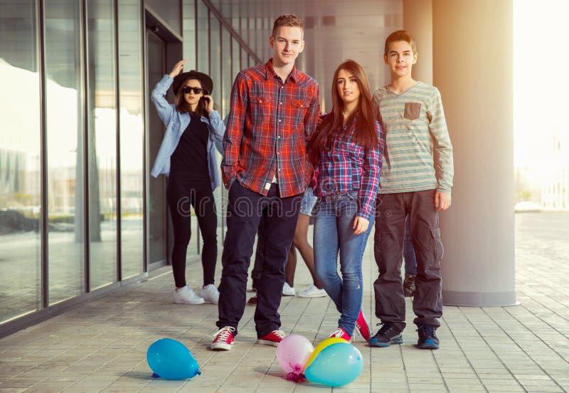 Las muchachas felices y los muchachos adolescentes que se divierten buen miden el tiempo al aire libre foto de archivo